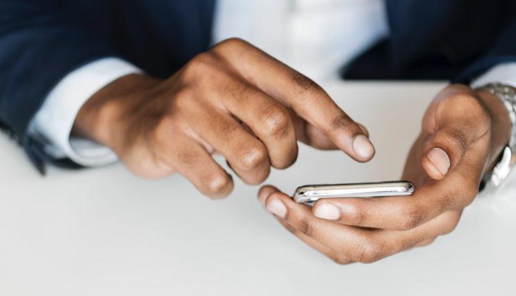 Antecipar o saque no Caixa Tem: enquadramento em mãos mexendo em celular