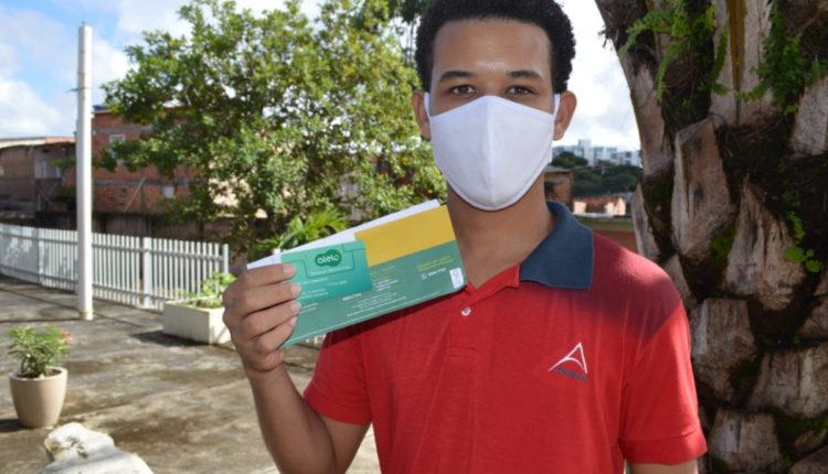 Vale-alimentação estudantil na Bahia: estudante segurando cartão de vale-alimentação. Ele está usando máscara para cobrir a boca
