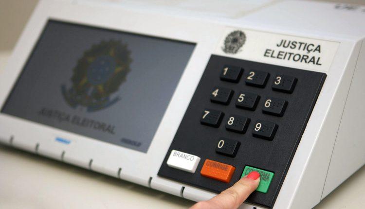 Obrigado a votar no segundo turno: enquadramento em dedo apertando tecla de urna eletrônica