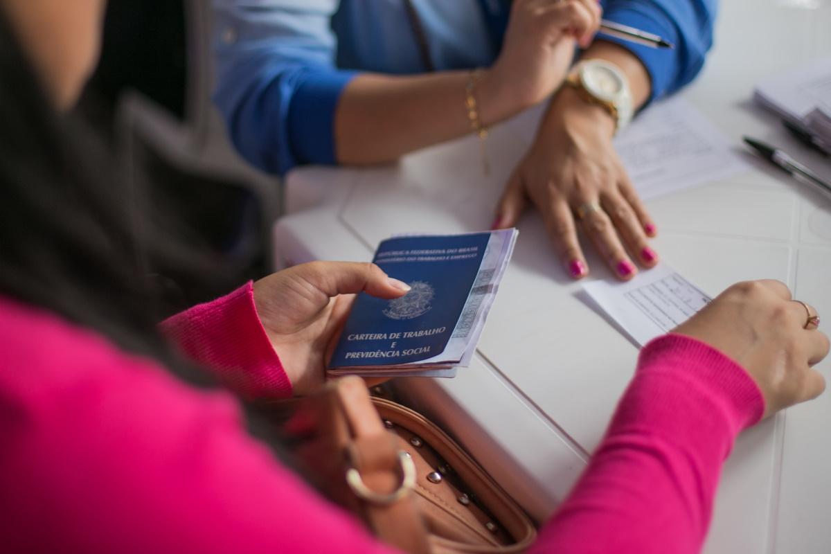 Prorrogação do seguro-desemprego: enquadramento em mão segurando carteira de trabalho