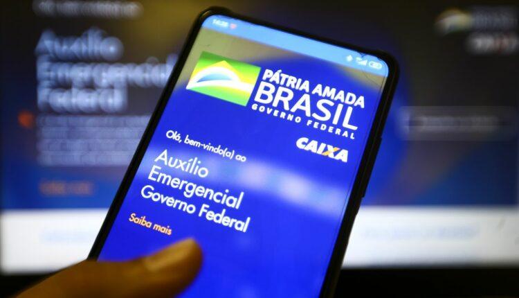 4ª parcela: mão segurando celular. Na tela, é possível ver página do auxílio emergencial