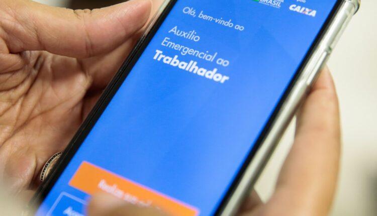 4ª parcela do auxílio: mão mexendo em celular. Na tela, é possível ver a página do auxílio emergencial