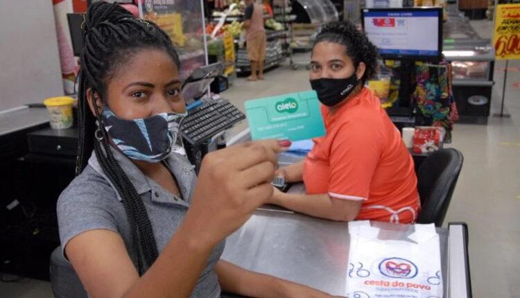 Vale-alimentação Bahia: mulher segurando cartão do vale-alimentação estudantil da Bahia